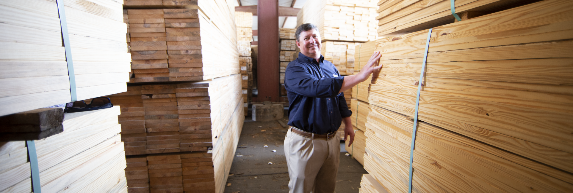 Fortress employee in warehouse with several stacks of wooden planks