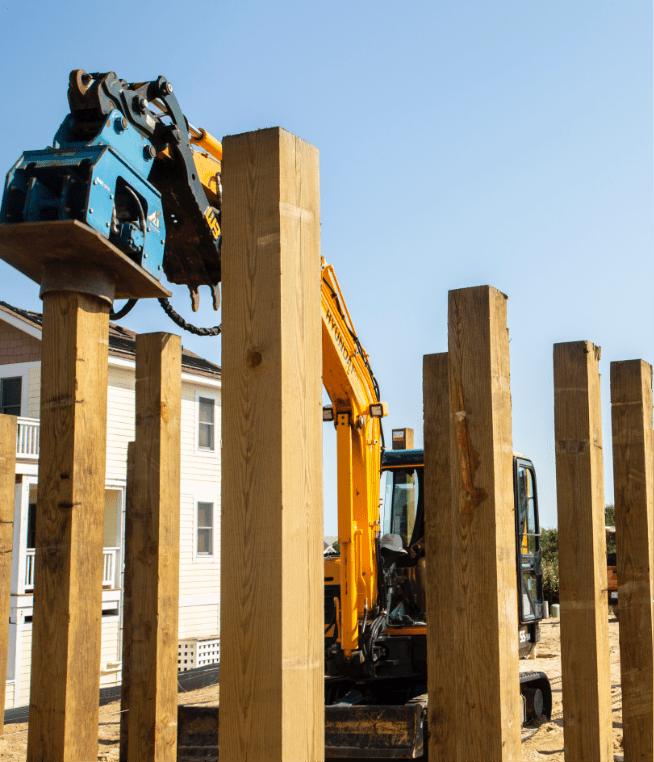 construction crane putting up wooden pillars