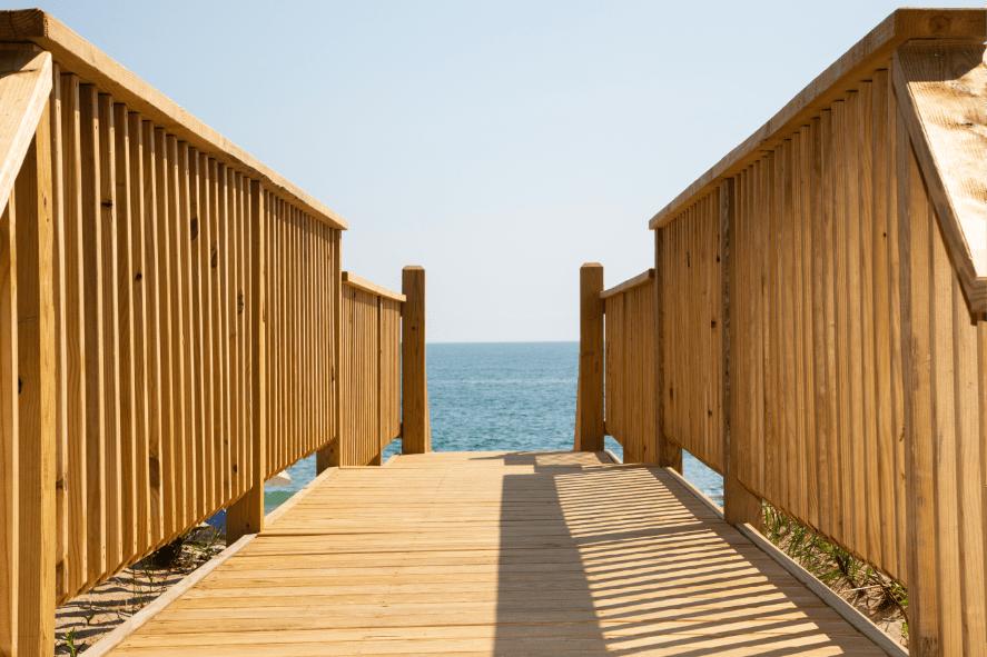 light wooden deck walkway to body of water