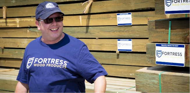 Man with blue Fortress shirt with hat and sunglass smile in front of Fortress labeled stacks of wood